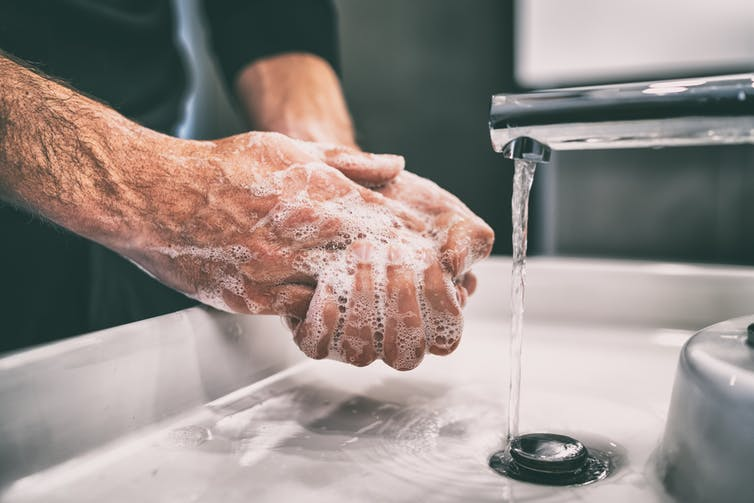 A man washing his hands with soap.