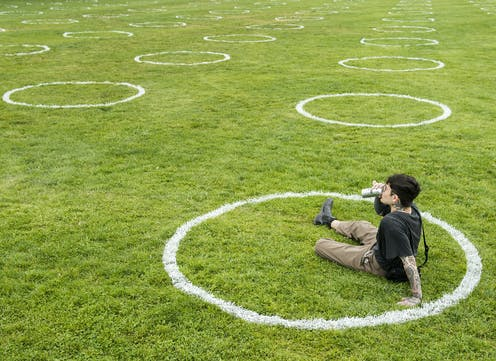 A man sits on the grass in a white circle, with dozens of empty white circles on the expanse of grass in the background