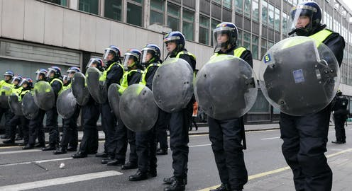 Riot police lined up with shields and helmets.