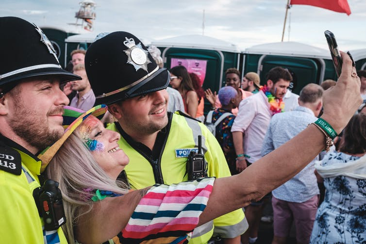Woman taking a selfie with two police officers.