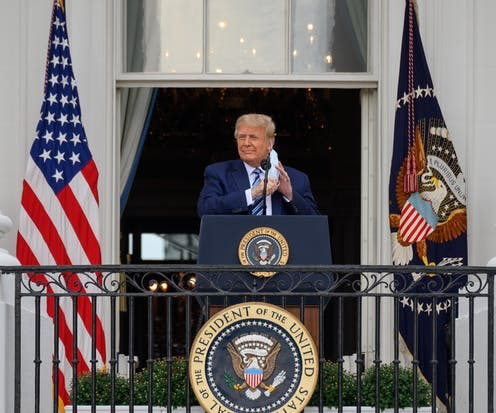 US president Donald Trump at the White House removing his mask before making an announcement.