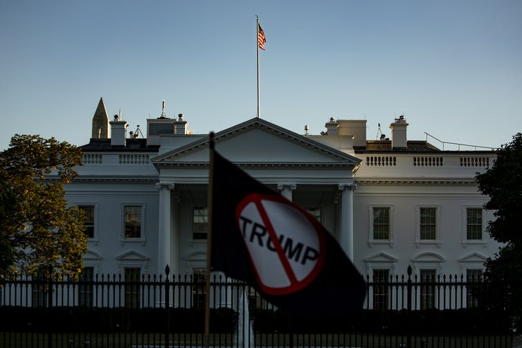 A protester holds up a 'Stop Trump' sign in front of the White House, October 2020.