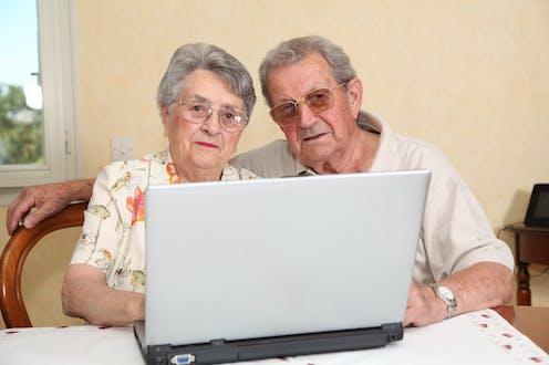 Dos personas mayores ante un ordenador.
