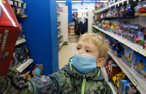 A boy reaches for a toy in a store.