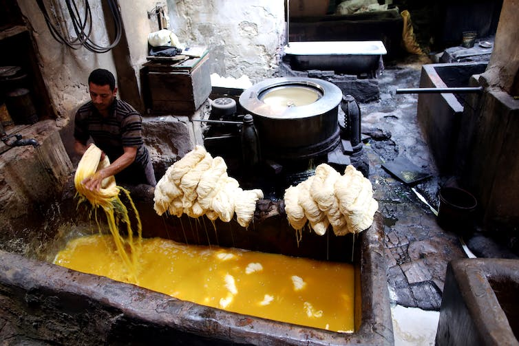 A worker removes a bundle of cotton yarn from a stone trough filled with yellow dye.