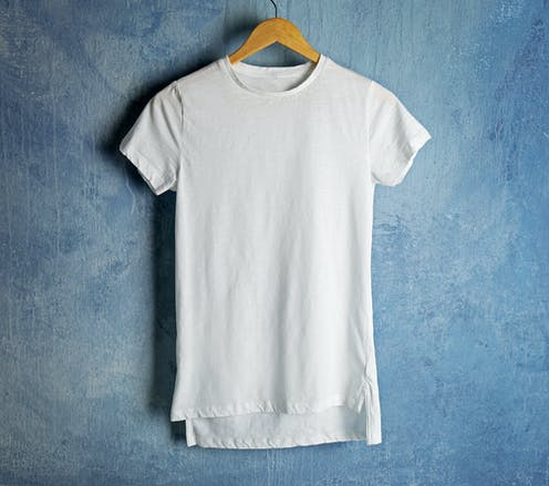 A white t-shirt on a hanger with a blue background.