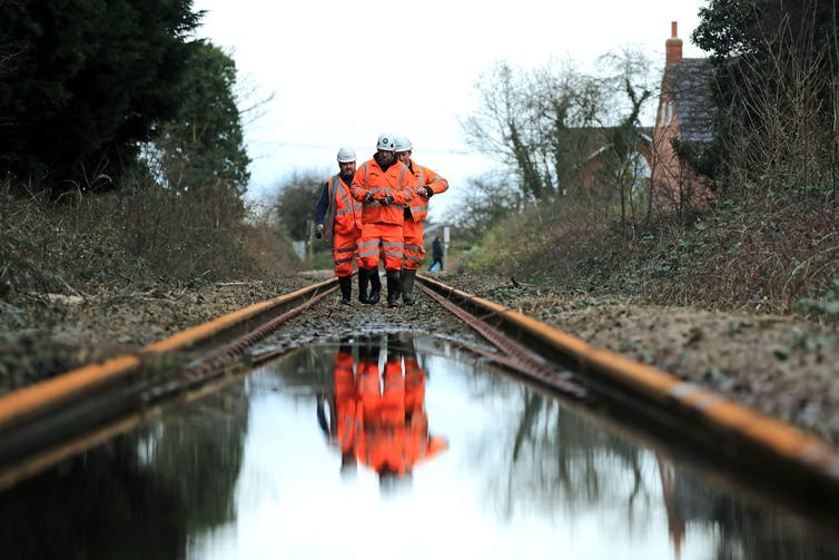 Three workers inspect a flooded railway track.