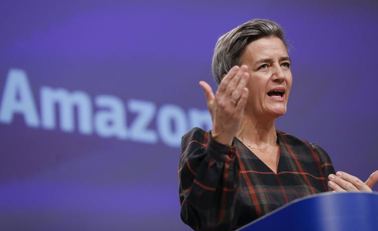 A woman gestures while speaking in front of an Amazon sign.