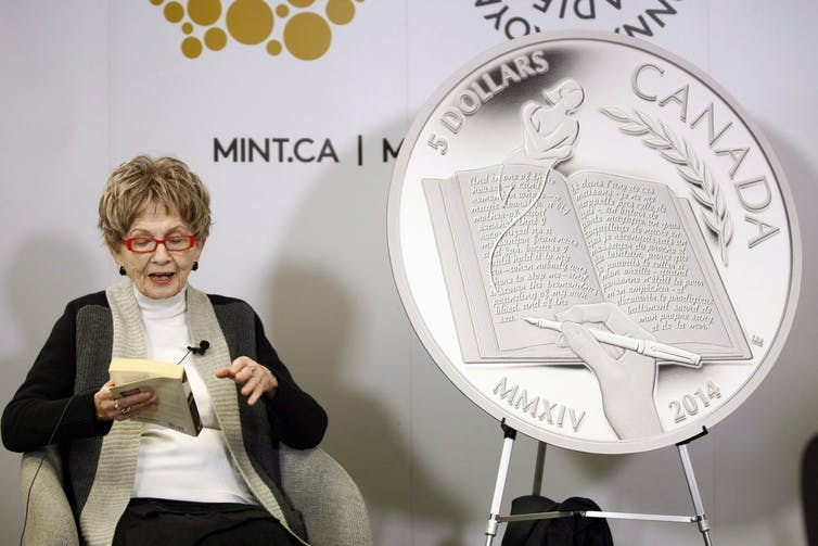 The author Alice Munro reads from her book while sitting next to a large replica of the $5 coin celebrating her achievements.