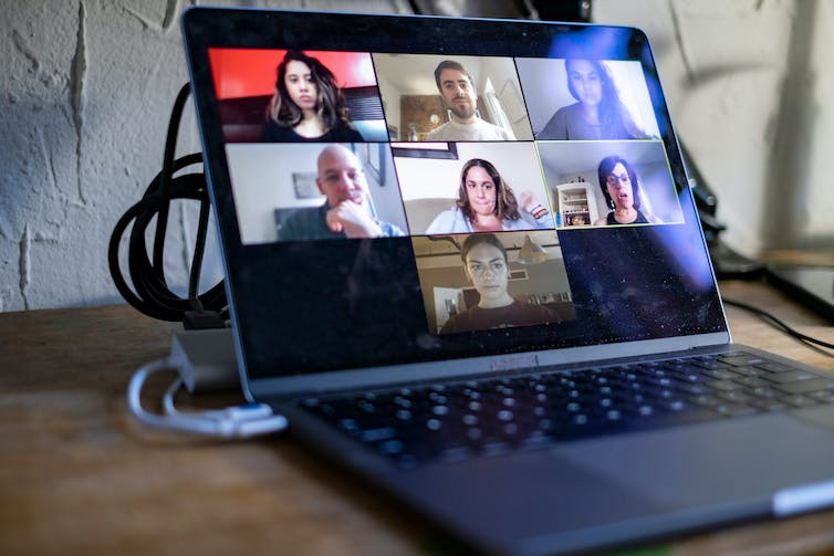laptop screen showing seven people participating in an online meeting.