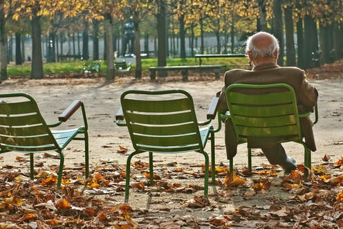 un hombre mayor en un parque en otoño sentado en una silla de espaldas