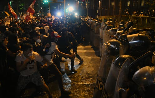 Police in riot gear with shields stand off against unarmed protesters holding signs and flags at night