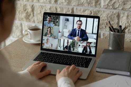 Hands on a laptop showing six people in business attire in a videoconference.