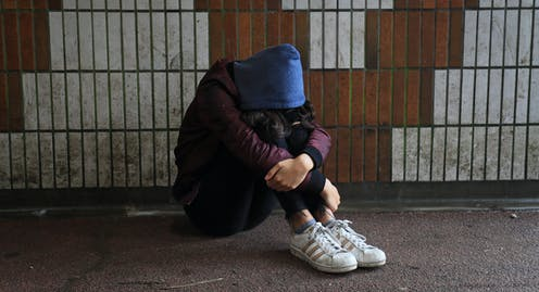 Teen wearing maroon jacket, blue hoodie and sneakers sits with her head between her knees