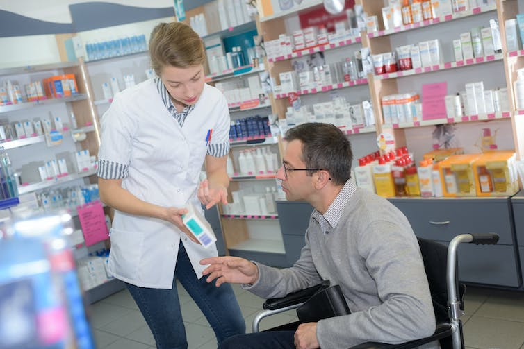 Pharmacist discussing a product with a man using a wheelchair