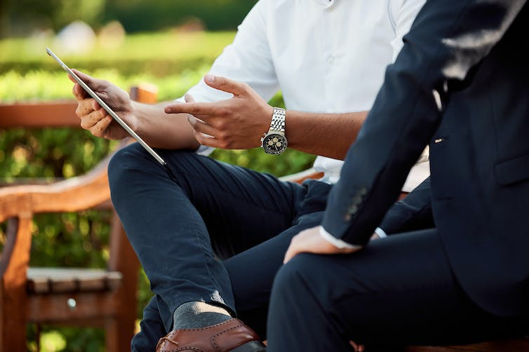 A man looks at a tablet as another man sits behind him in an outdoor setting.