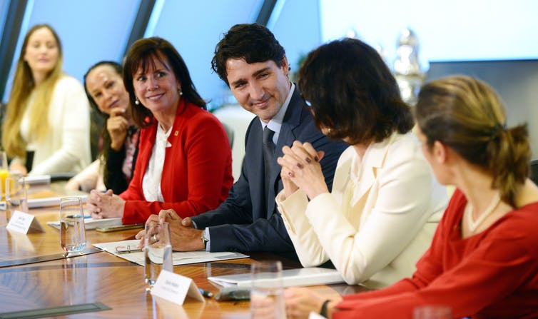 Justin Trudeau sits on a panel with women.