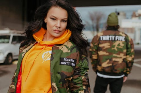 A woman and man stand in camo-style bomber jackets.