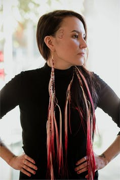 A woman stands in beaded earrings.