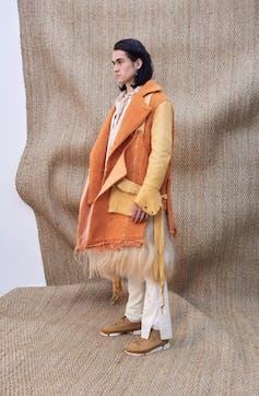 A man stands in orange coat.