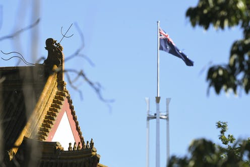 Chinese Embassy roofline next to the Parliament House flag.