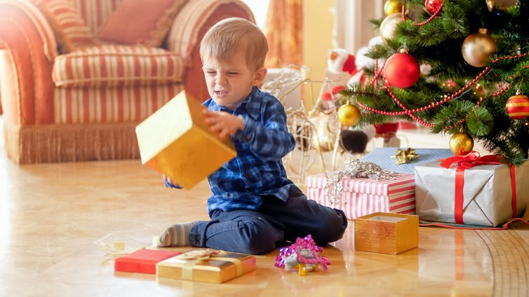 A toddler looking unhappy at gift