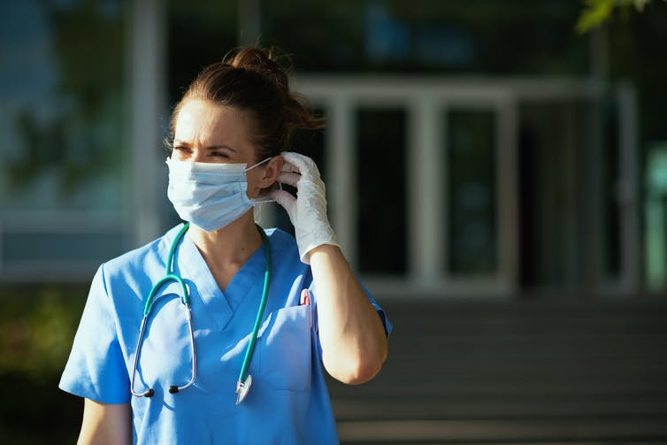 A health-care worker stands outdoors, adjusting her mask.