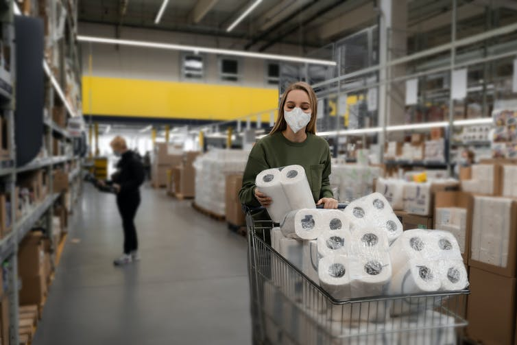 A woman wearing a surgical mask pushing a cart full of toilet paper