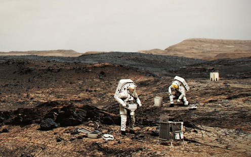 An artist drawing of twopeople in spacesuits walking on Mars.