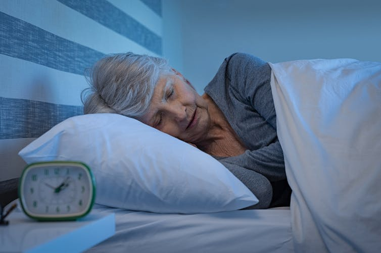 An elderly lady in bed is asleep
