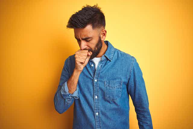 Man coughing into his hand