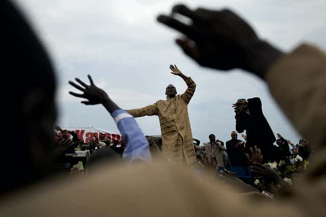 In the foreground, hands are raised in the air and beyond them, a man in traditional attire raises his own hands heavenward.