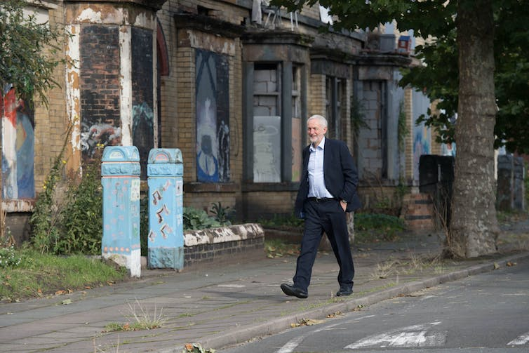 A white man in a suit walks down a road of derelict terraced houses.