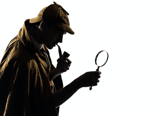Silhouette of man with deerstalker hat, pipe and magnifying glass.