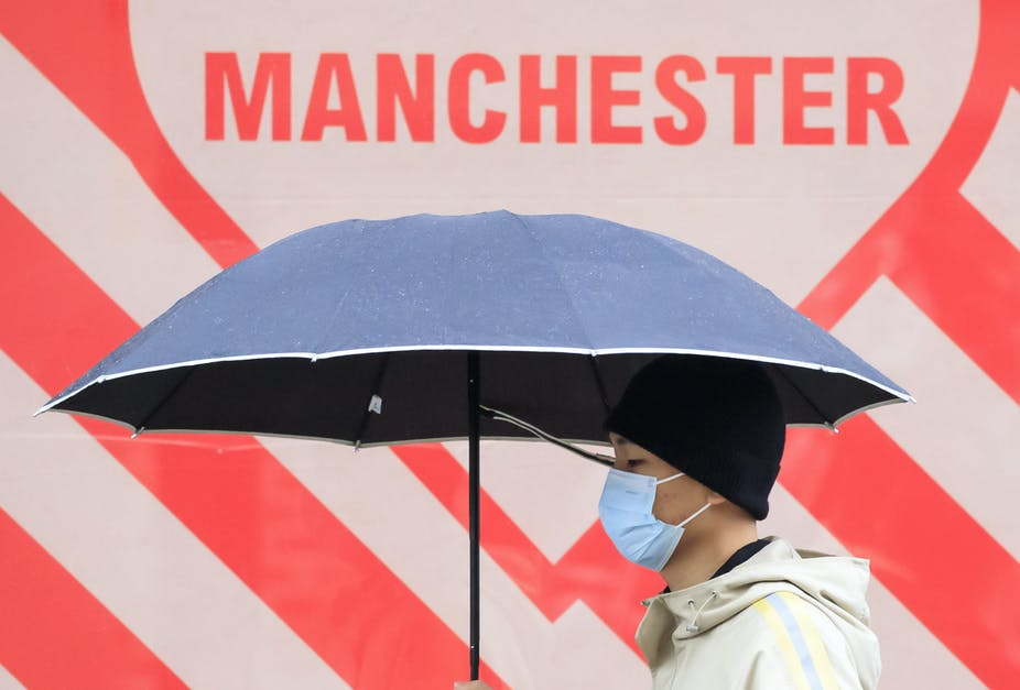 A man wearing a mask carrying an umbrella walks past a sign that says MANCHESTER