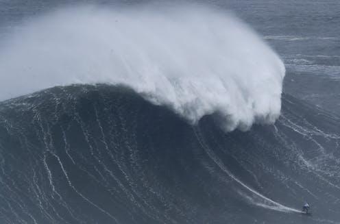 Maya Gabiera surfing a huge wave.