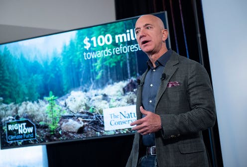 Jeff Bezos stands in front of a photo of a forest