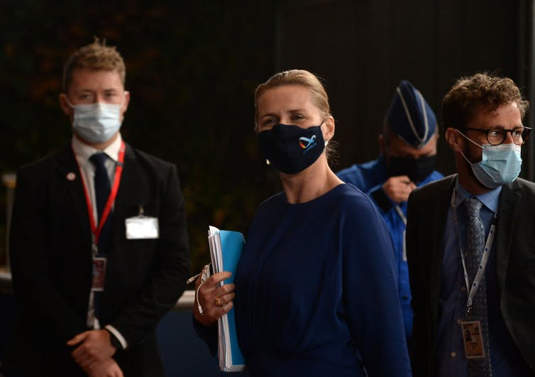 Mette Frederiksen wearing a black mask and holding a folder.