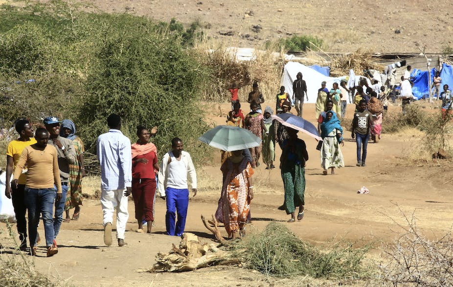 Men and women walking on a path in open country, a tent type of shelter in the background