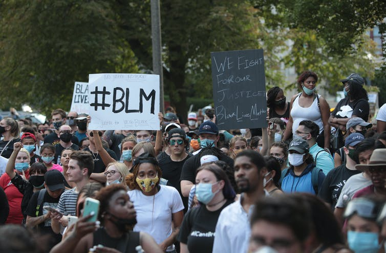 Crowd of mostly Black protesters in face masks hold up BLM and other racial justice signs