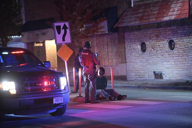 Man sits handcuffed on a curb while police stand over him at night.
