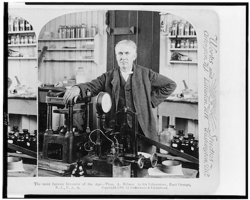 A black-and-white photograph of and older white man in a laboratory circa 1900