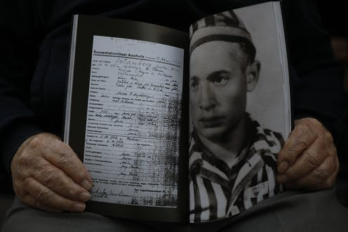 A man holds a photo of himself and his concentration camp record