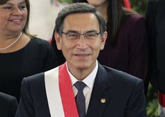 A man with glasses and dark hair smiles.