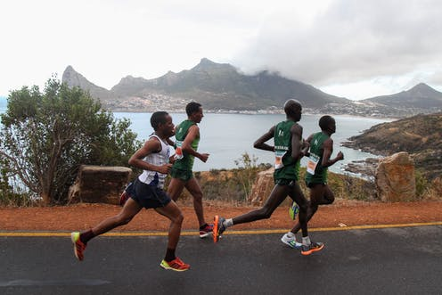 Four men run in a group, wearing vests and shorts. In the background, a view of the Cape Town bay with misty mountains.