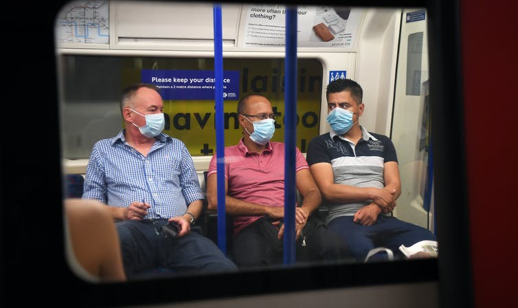 Three men wearing masks on the London underground.