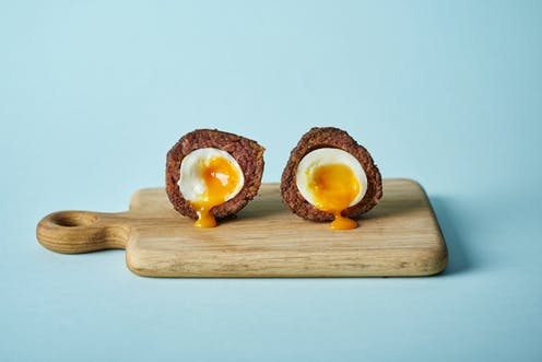 A scotch egg cut in two on a wooden board