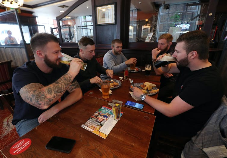 A group of men sit around a table drinking beers while two of them eat.