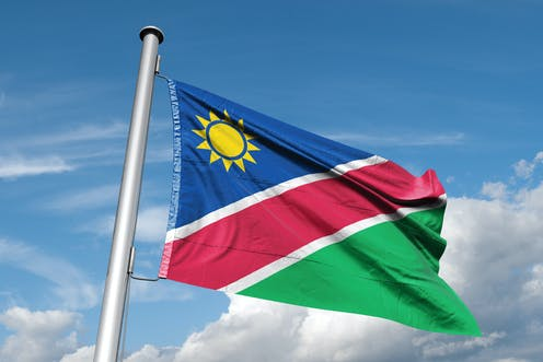 A flag flies in a blue sky with white clouds. The flag has a yellow sun against a triangle of blue, a red stripe in the centre and a green triangle below.