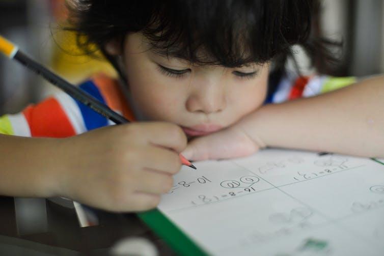 Young boy doing maths homework